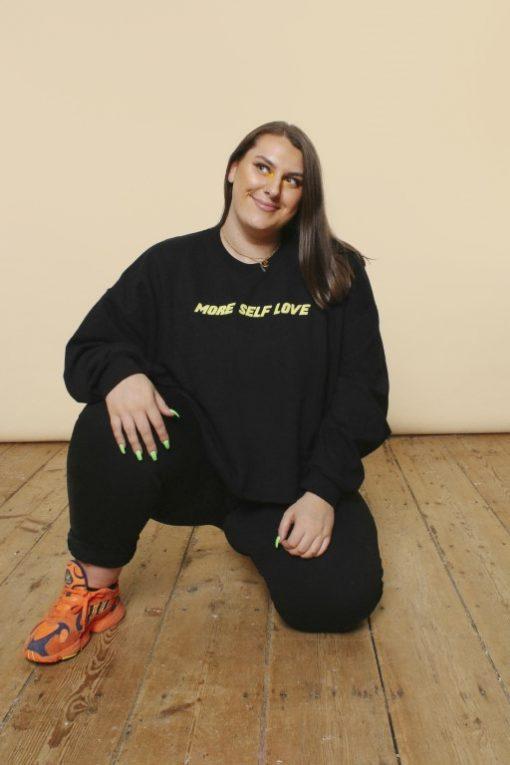 Girl wearing black cropped slogan sweatshirt